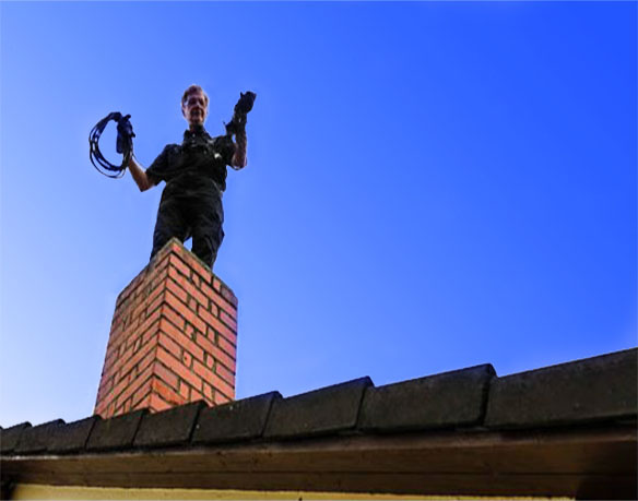 on roof preparing chimney sweep