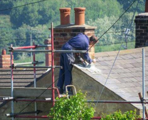 on roof top repairing chimney